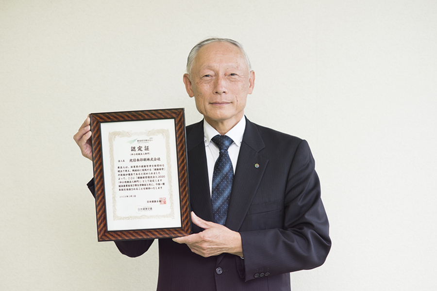 健康経営優良法人認定証を持つ川口社長